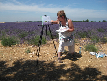 Woman painting in front of lavender fields during Walk the Arts painting workshops in France