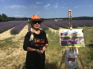 Woman in front of her painting of the lavender fields during our art workshop in Provence