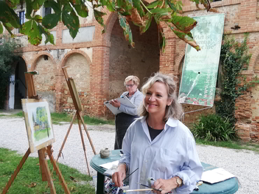 Woman in front of her painting during our art classes in Italy for all levels