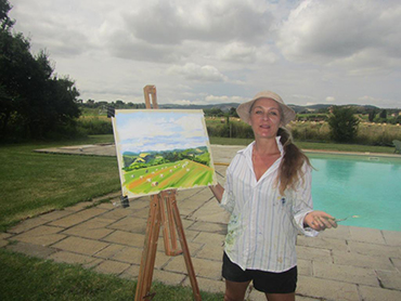Artist in front of her painting during Walk the Arts art workshop in Italy