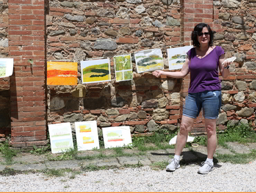 Woman in front of her paintings during our art retreats in Tuscany Italy for all levels and mediums